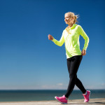fitness and lifestyle concept - woman walking outdoors